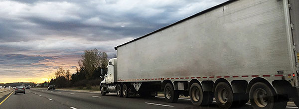 White freight truck on highway during cloudy sunset