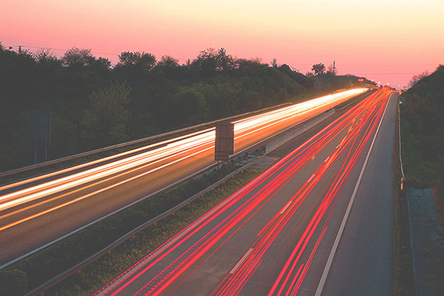 Cars in movement on a highway at sunset